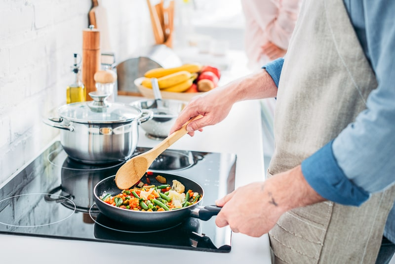 Person holding pan with vegetables and wooden spoon cooking