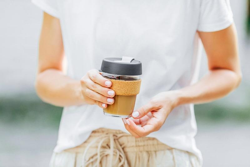 Person holding reusable coffee mug