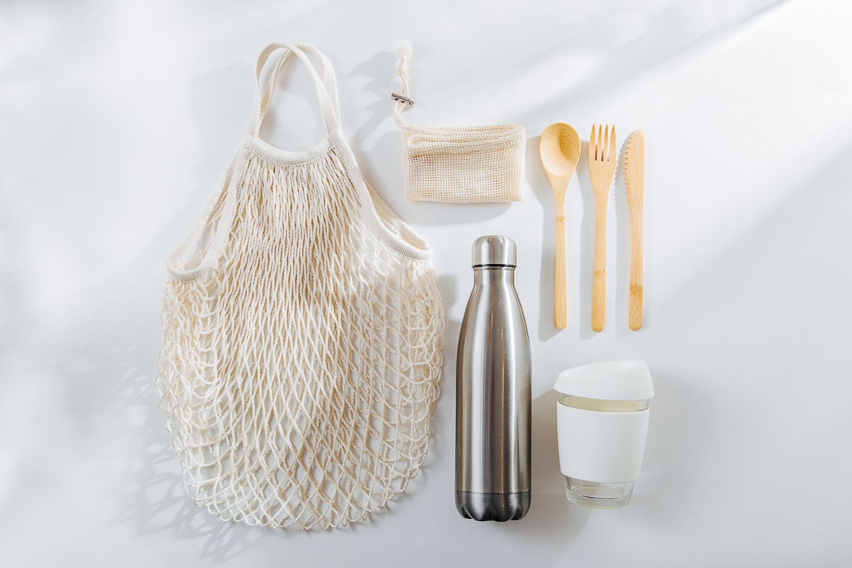 Wooden utensils reusable water bottle coffee mug and grocery bag how to reduce plastic waste at home reviving simple