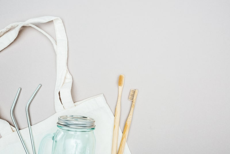 Bamboo toothbrushes mason jar and reusable straws in front of reusable bag less waste