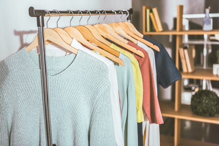 shirts and sweaters hanging on metal bar in room not buying new clothes for a year