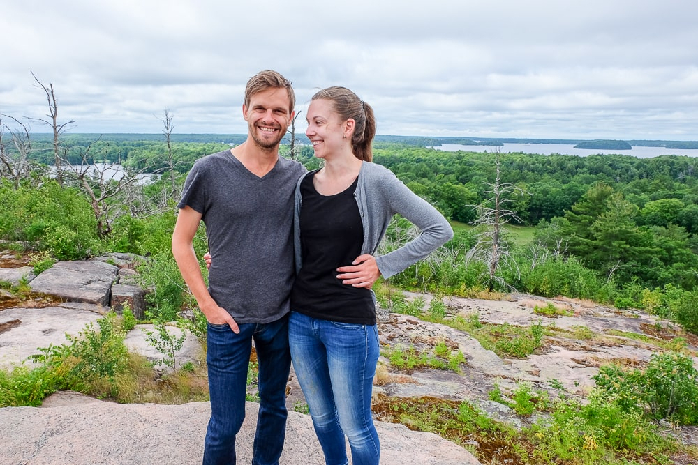 couple standing with forest views behind reviving simple