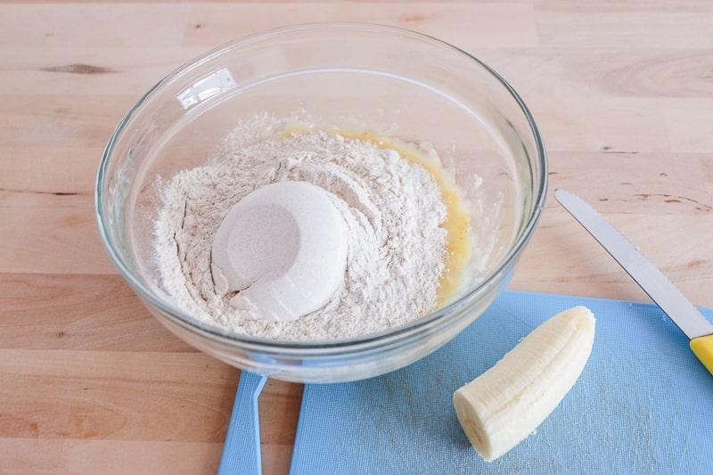 flour in bowl on wooden table with banana vegan buckwheat banana pancakes