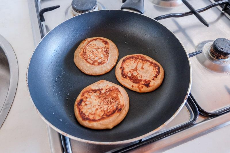 flipped over pancakes in frying pan vegan buckwheat banana pancakes