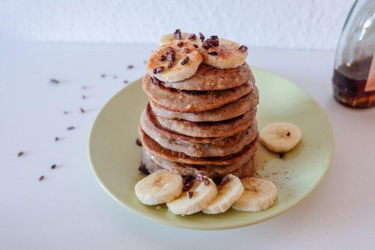 vegan buckwheat banana pancakes with syrup and sliced banana on plate