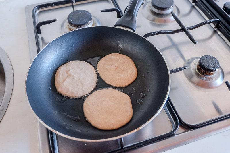 pancakes cooking in black frying pan vegan buckwheat banana pancakes
