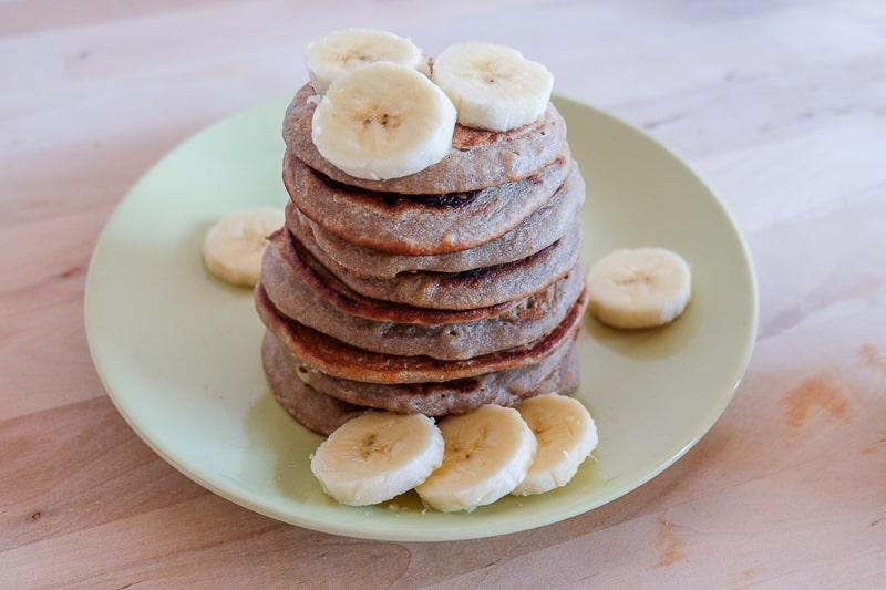 vegan buckwheat banana pancakes in stack on plate with banana slices