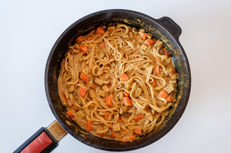 cast iron pan on white table full of coconut curry noodles