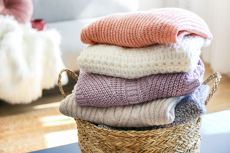 basket full of cozy knitted sweaters on room