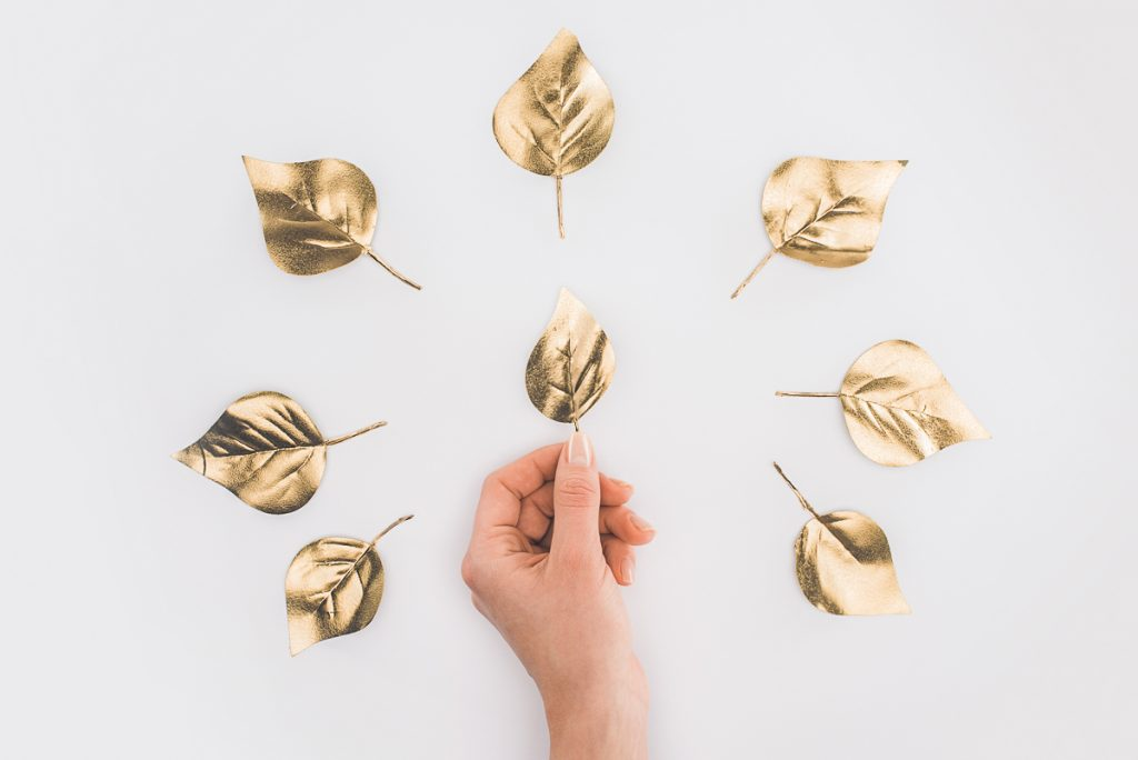 golden leaves with hand on white background benefits of frugal living