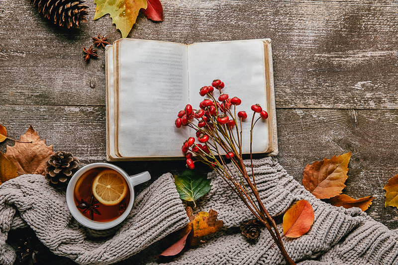 open book with flower and hot drink beside on wooden floor