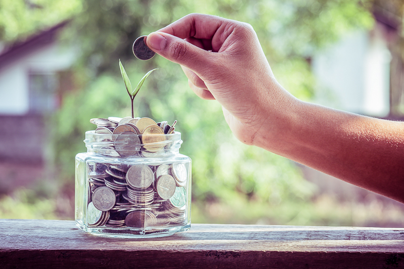 hand placing coins in jar on ledge benefits of frugal living