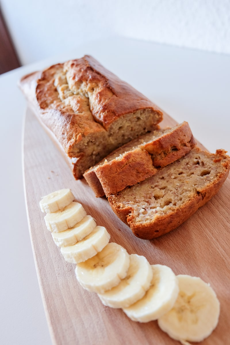 easy banana bread on wooden cutting board with sliced bananas