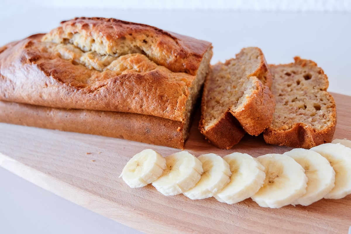 easy banana bread cut with sliced bananas on wooden cutting board