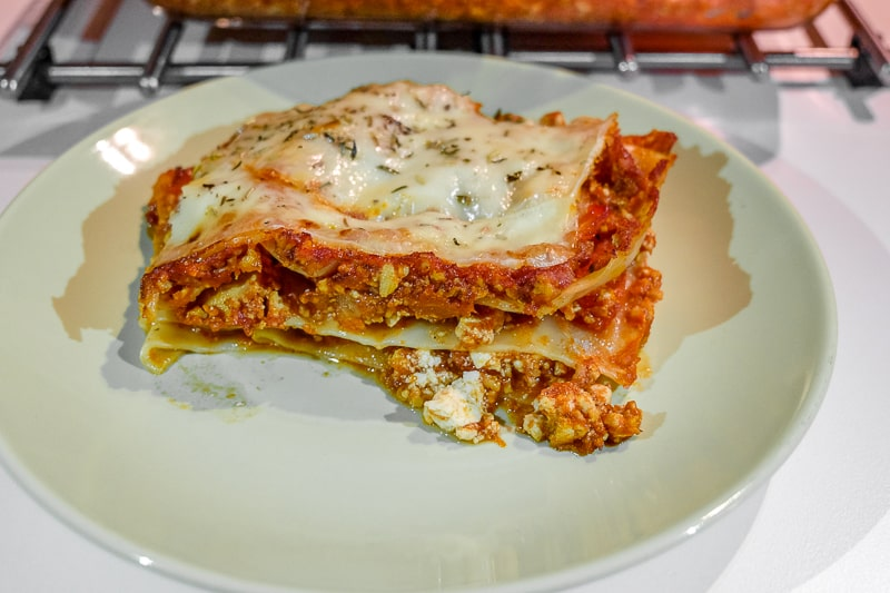 slice of layered vegetarian lasagna on green plate on table