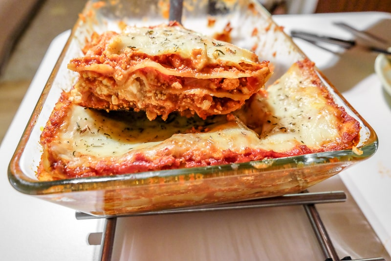 lasagna slice lifted from pan over table