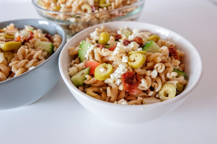 white bowl of mediterranean pasta salad on table