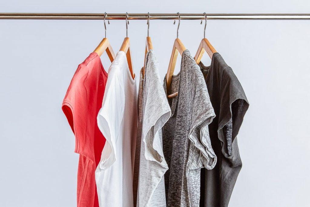 five shirts on hangers on metal rod not buying new clothes for a year reviving simple