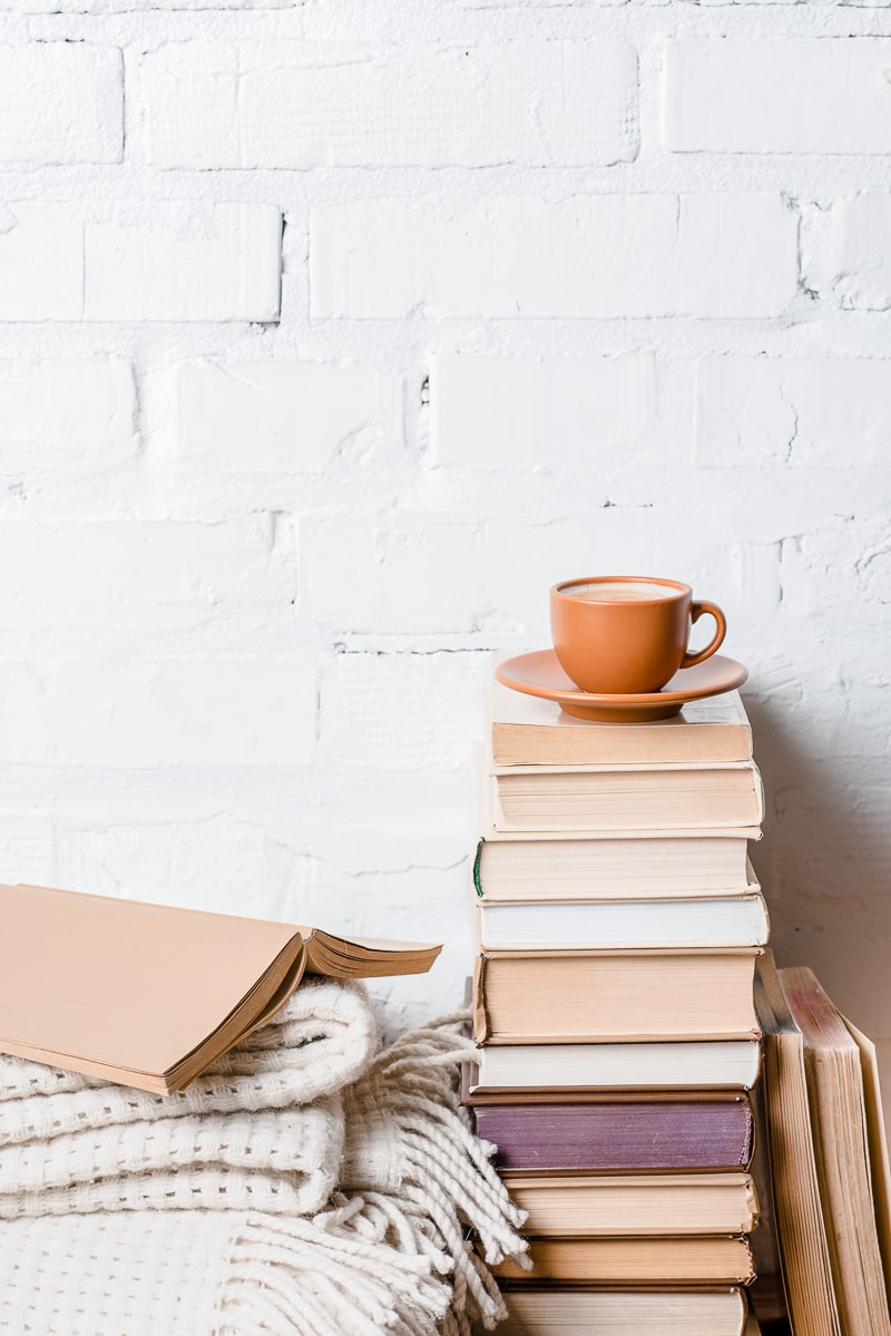 mug and saucer on stack of books beside bed with white brick behind