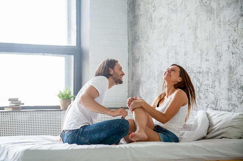 man and woman laughing on bed in bright room