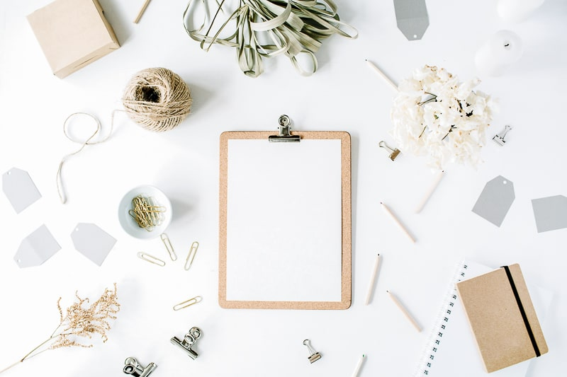 clipboard with blank paper and art supplies on desk
