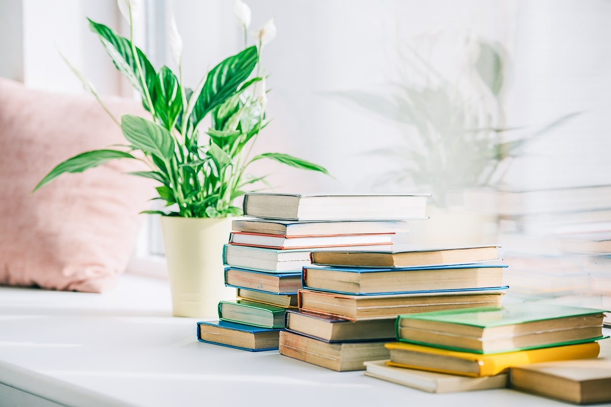 books on shelf with plant beside simple living quotes