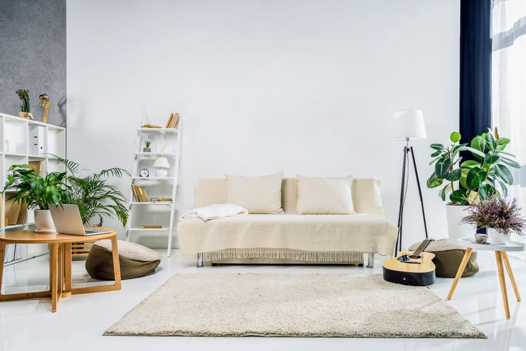 couch in open room with shelves and guitar close by benefits of living in smaller space
