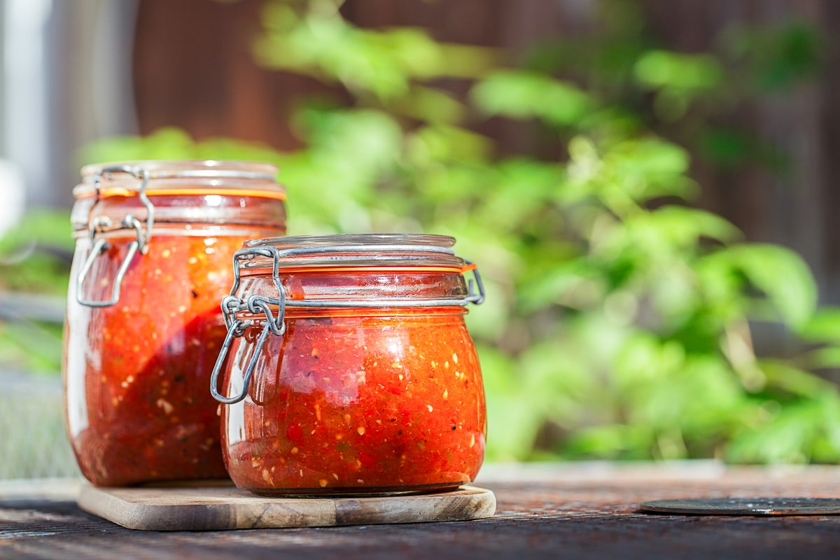 clear jars of red tomato paste outside how to reduce food waste at home