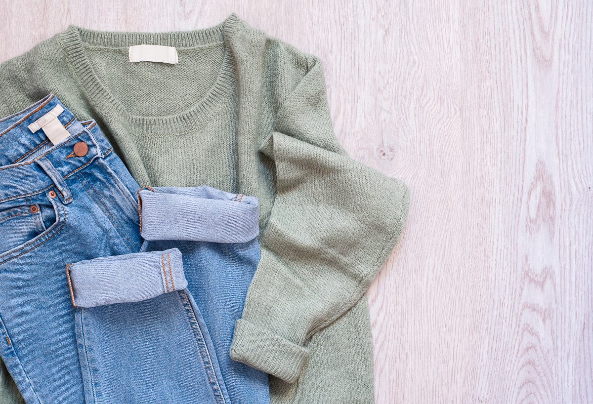 green sweater and blue jeans on wooden table how to stop impulse buying